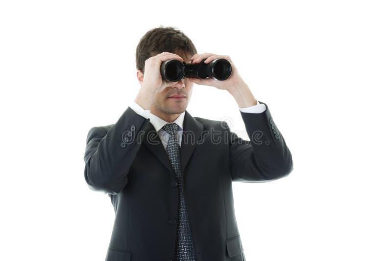 Uomo d'affari che osserva con il binocolo fotografia stock