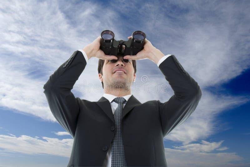 Uomo d'affari che osserva con il binocolo fotografia stock libera da diritti