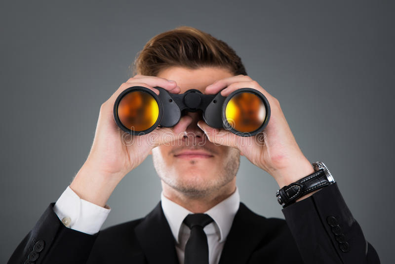 Uomo d'affari che osserva tramite il binocolo immagini stock