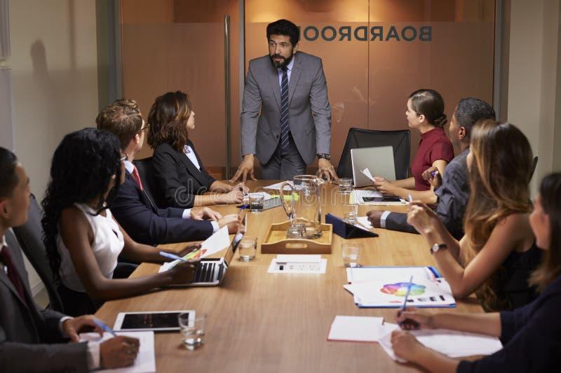 Uomo d'affari che parla ai colleghi ad una riunione della sala del consiglio fotografia stock