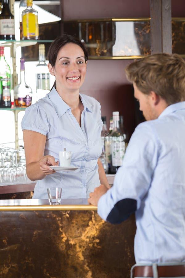 Uomo d'affari che parla con cameriera al banco nella barra fotografie stock libere da diritti