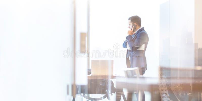 Uomo d'affari che parla su un telefono cellulare in ufficio corporativo mentre guardando attraverso la finestra fotografia stock libera da diritti