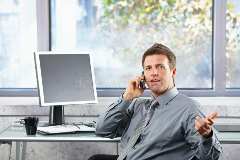 Uomo d'affari che parla sul mobile allo scrittorio fotografia stock