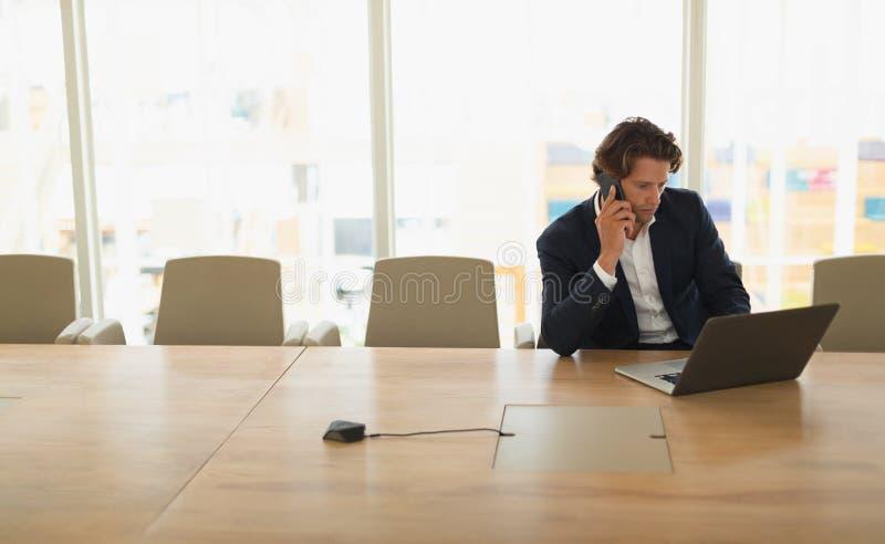 Uomo d'affari che parla sul telefono cellulare mentre facendo uso del computer portatile nell'auditorium fotografie stock