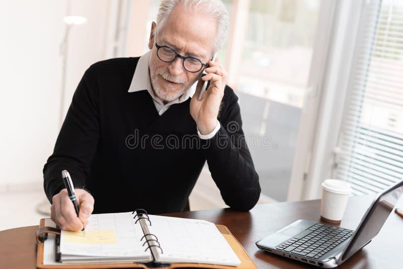 Uomo d'affari che parla sul telefono cellulare per prendere un appuntamento immagine stock libera da diritti