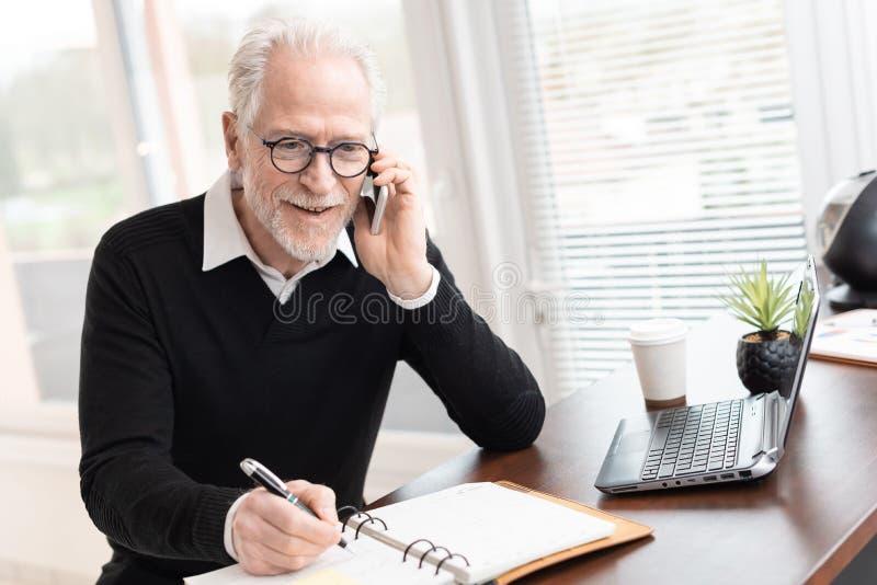 Uomo d'affari che parla sul telefono cellulare per prendere un appuntamento fotografia stock