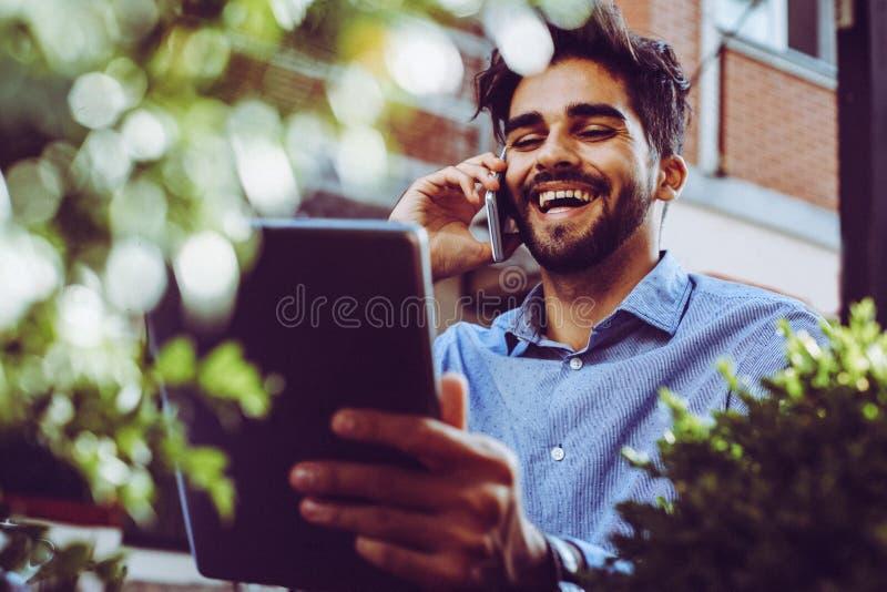 Uomo d'affari che parla sullo Smart Phone e che per mezzo della compressa digitale fotografie stock