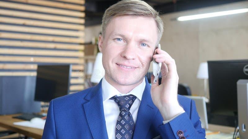 Uomo d'affari che parla sullo smartphone in ufficio fotografie stock libere da diritti