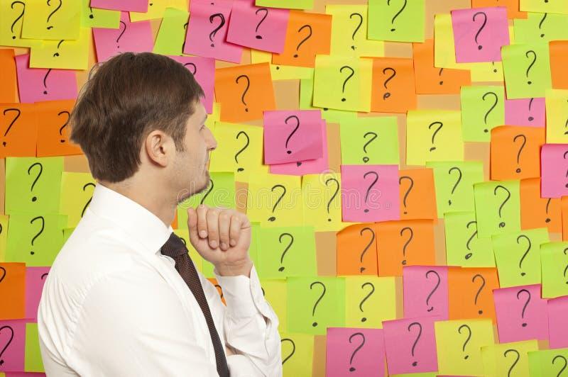 Uomo d'affari che pensa con i punti interrogativi scritti fotografie stock