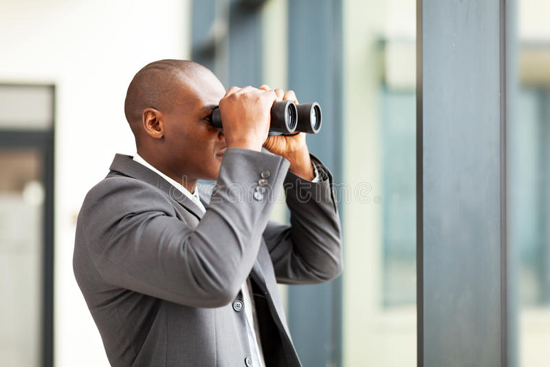 Uomo d'affari che per mezzo del binocolo fotografia stock