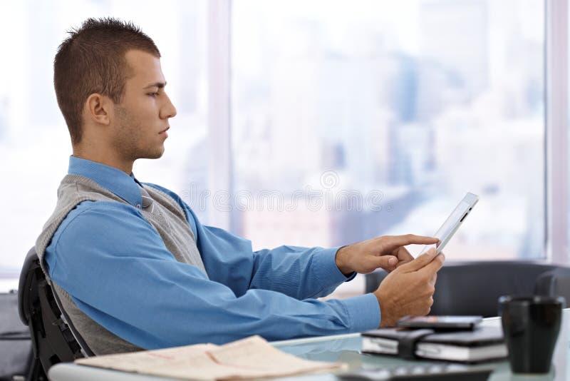 Uomo d'affari che per mezzo del calcolatore del ridurre in pani immagini stock libere da diritti