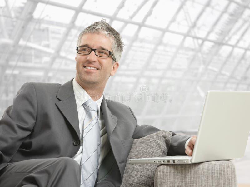 Uomo d'affari che per mezzo del computer portatile immagini stock libere da diritti