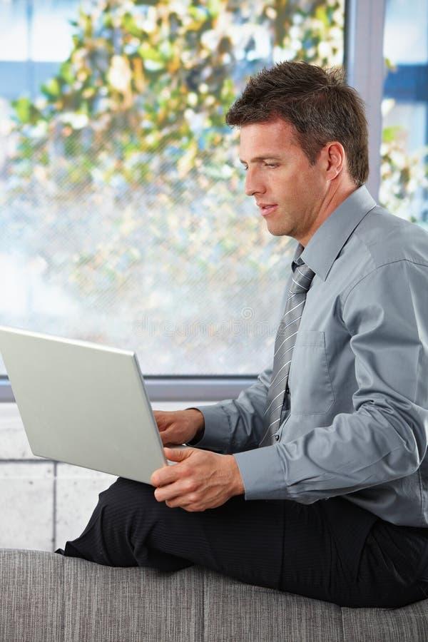 Uomo d'affari che per mezzo del computer portatile sullo strato immagini stock libere da diritti