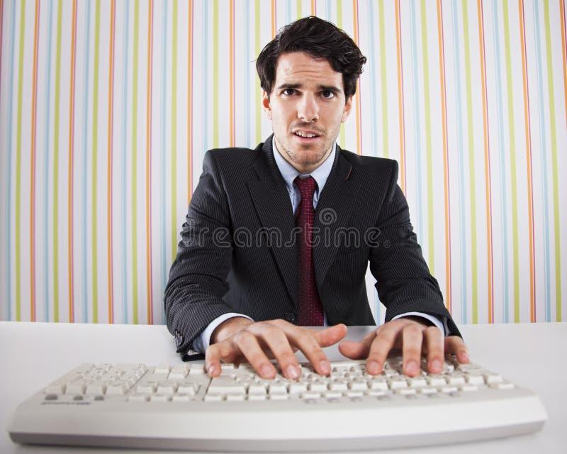 Uomo d'affari che per mezzo del suo calcolatore immagine stock