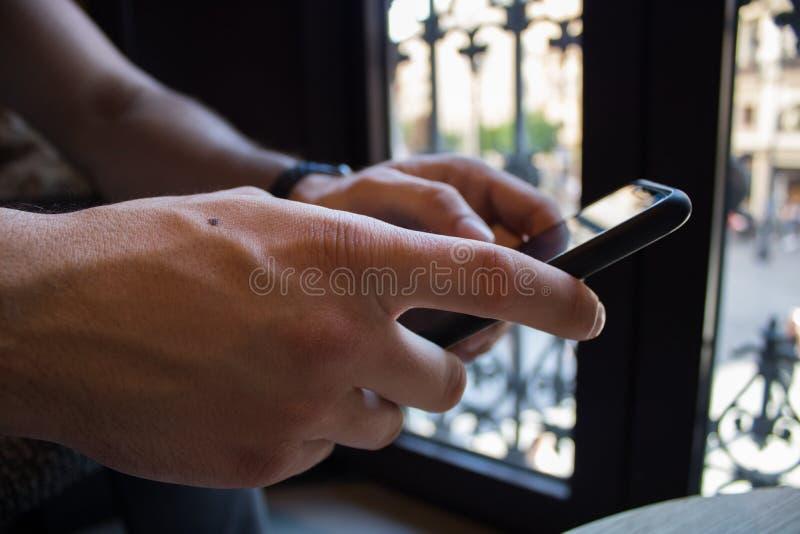 Uomo d'affari che per mezzo del suo Smart Phone dentro una caffetteria Primo piano delle mani fotografie stock libere da diritti