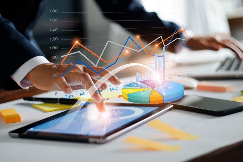 Uomo d'affari che per mezzo della compressa e del computer portatile che analizzano le vendite dati ed il grafico del grafico del immagine stock