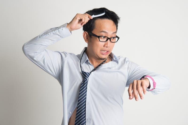 Uomo d'affari che pettina capelli nella mattina nella fretta immagine stock