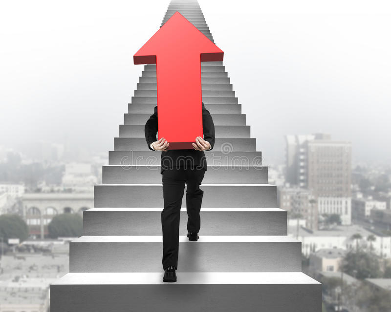 Uomo d'affari che porta il segno rosso della freccia sulle scale con la scena urbana fotografie stock libere da diritti