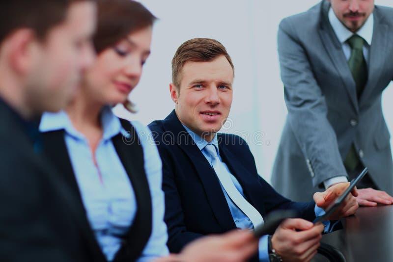 Uomo d'affari che posa nella sala riunioni mentre i colleghi stanno lavorando dietro fotografie stock libere da diritti