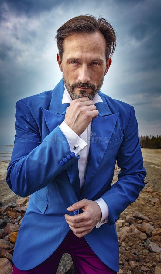 Uomo d'affari che posa sulla spiaggia, fine sul ritratto, giorno, all'aperto immagini stock libere da diritti