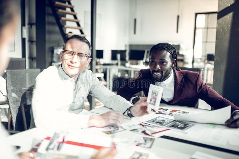 Uomo d'affari che possiede rivista di moda che parla con suoi impiegati fotografia stock