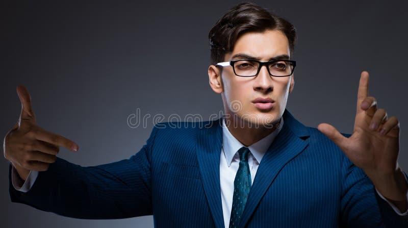 Uomo d'affari che preme i bottoni virtuali su fondo grigio fotografia stock
