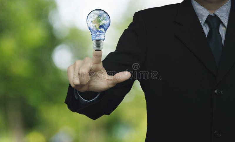 Uomo d'affari che preme il globo della terra in lampadina sopra verde della sfuocatura immagini stock