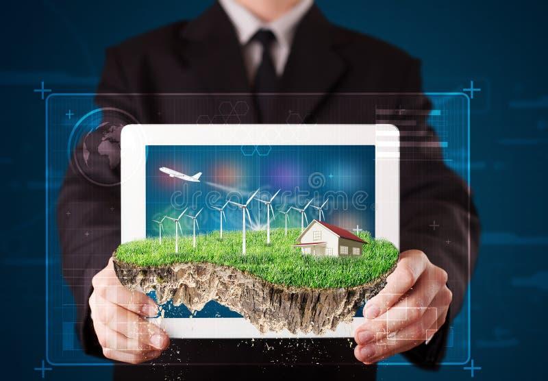 Uomo d'affari che presenta una terra perfetta di ecologia con una casa e w fotografia stock libera da diritti