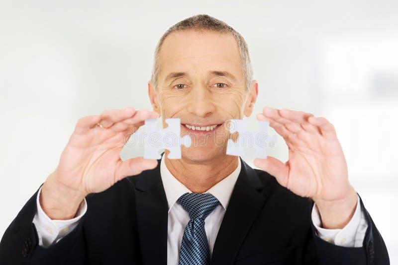 Uomo d'affari che prova a collegare i pezzi di puzzle fotografia stock