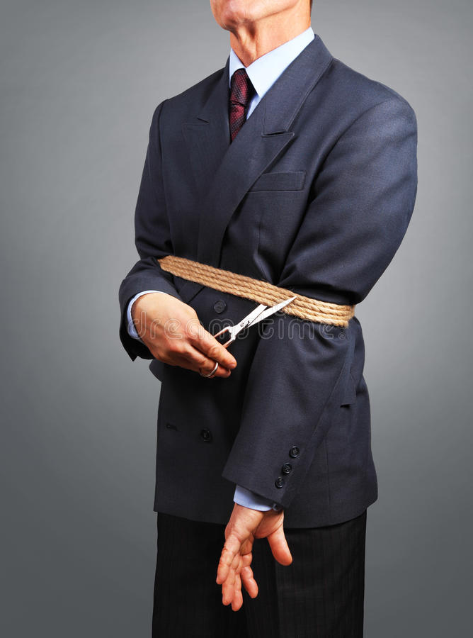Uomo d'affari che prova a liberarsi dei fetters fotografie stock