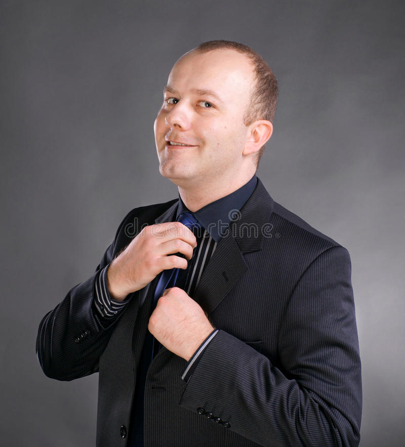 Uomo d'affari che regola la sua cravatta fotografie stock