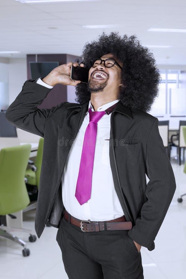 Uomo d'affari che ride sul telefono immagine stock