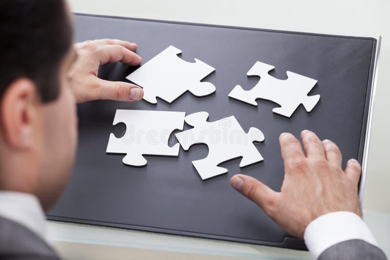 Uomo d'affari che risolve puzzle fotografie stock