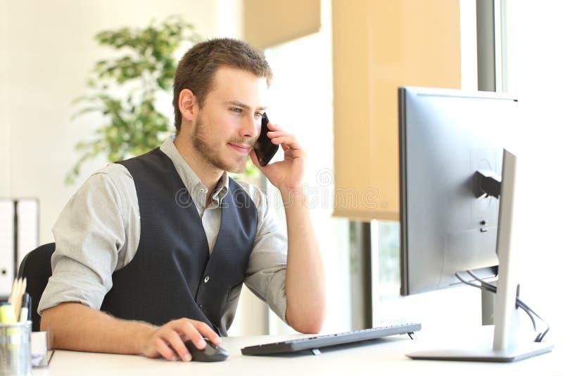 Uomo d'affari che rivolge al telefono e che per mezzo di un computer fotografia stock libera da diritti