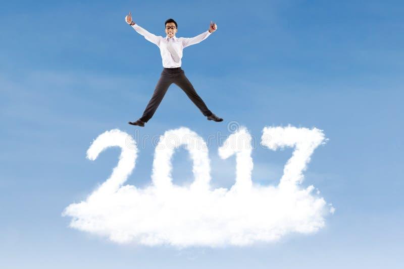 Uomo d'affari che salta sopra il numero a forma di 2017 della nuvola fotografia stock