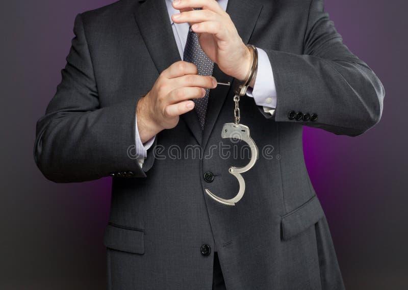 Uomo d'affari che sblocca le manette immagine stock libera da diritti