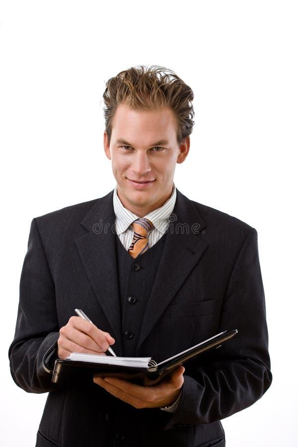 Uomo d'affari che scrive al taccuino fotografie stock