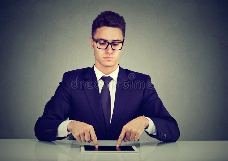 Uomo d'affari che scrive con le dita sul suo computer della compressa immagine stock