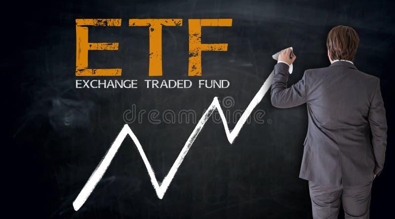 Uomo d'affari che scrive ETF sul concetto della lavagna immagini stock
