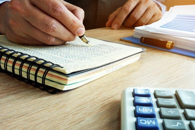 Uomo d'affari che scrive i risultati finanziari in libro Concetto di contabilità fotografie stock libere da diritti