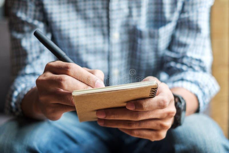 Uomo d'affari che scrive qualcosa sul taccuino nell'ufficio, mano della penna di tenuta dell'uomo con la firma sul rapporto della fotografia stock