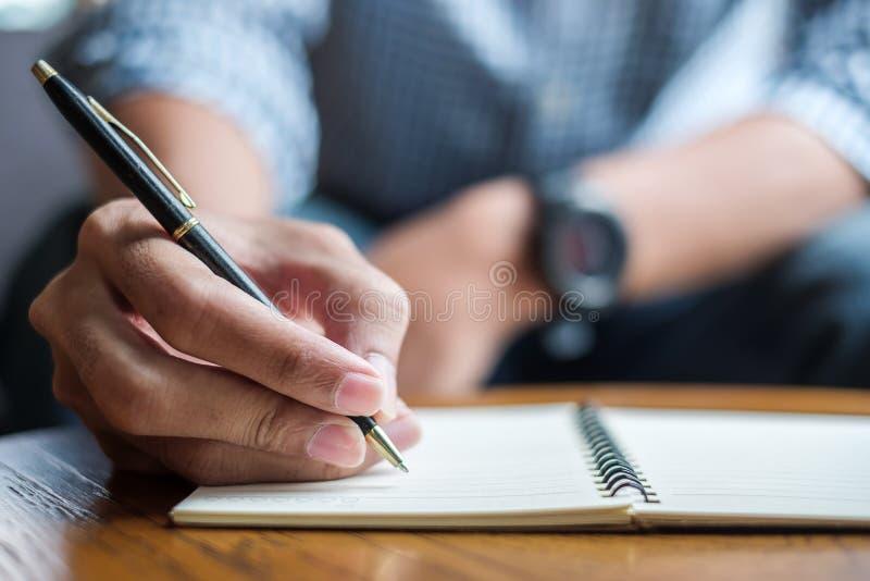 Uomo d'affari che scrive qualcosa sul taccuino nell'ufficio, mano della penna di tenuta dell'uomo con la firma sul rapporto della fotografie stock libere da diritti
