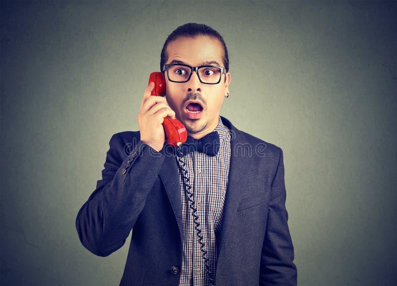 Uomo d'affari che sembra colpito mentre parlando sul telefono fotografia stock libera da diritti