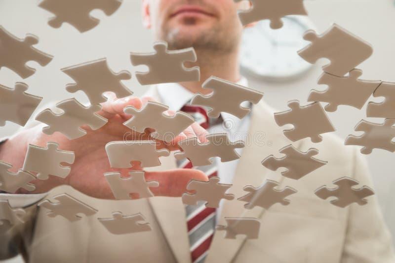Uomo d'affari che separa puzzle immagini stock