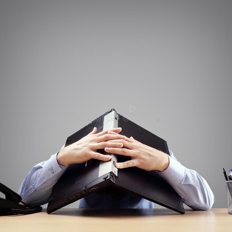 Uomo d'affari che seppellisce la sua testa sotto un computer portatile che chiede l'aiuto fotografie stock