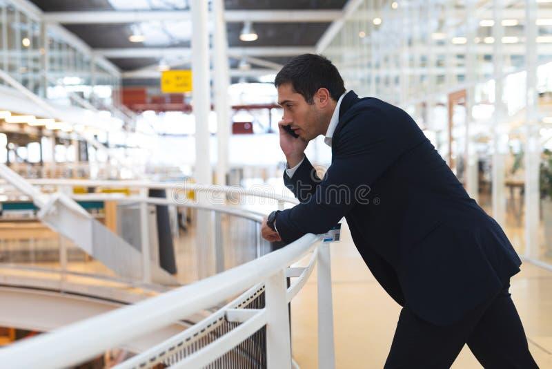 Uomo d'affari che si appoggia inferriata e che parla sul telefono cellulare in un ufficio moderno fotografia stock