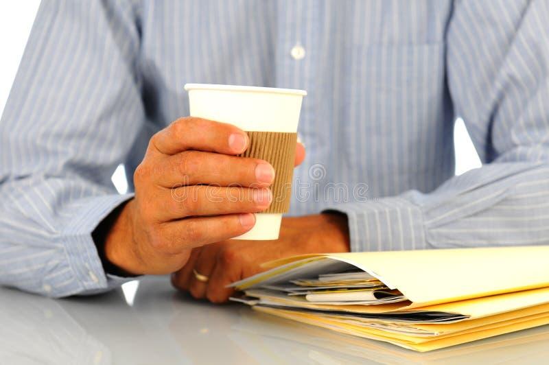 Uomo d'affari che si appoggia sullo scrittorio con la tazza di caffè immagine stock libera da diritti