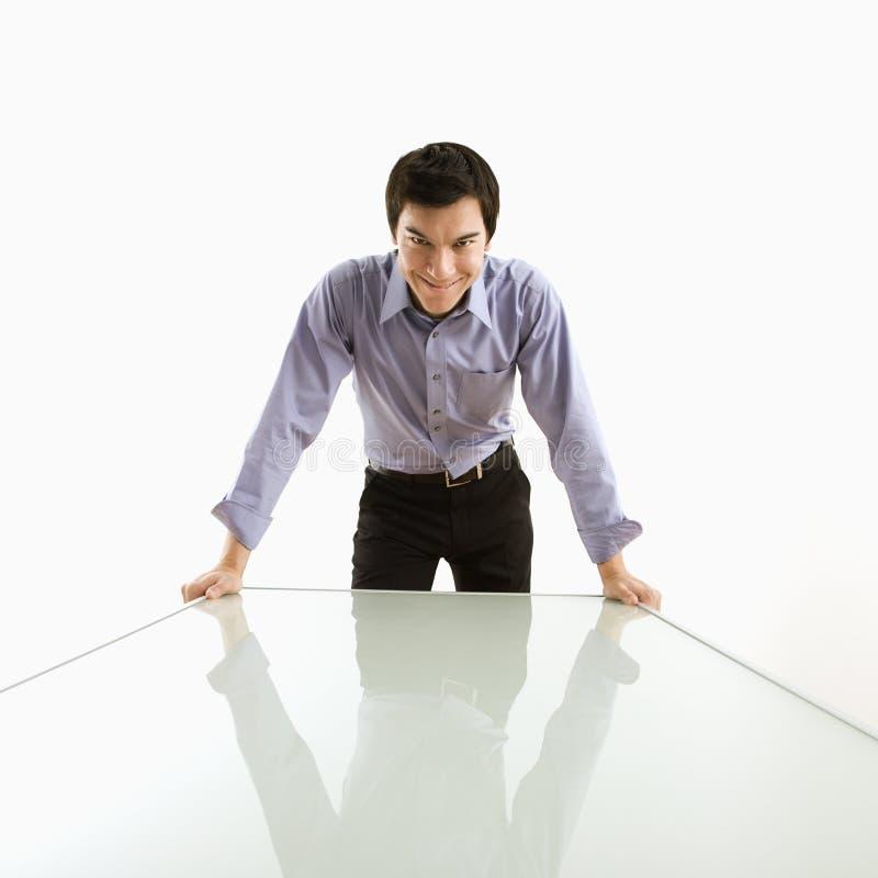 Uomo d'affari che si leva in piedi alla tabella immagini stock