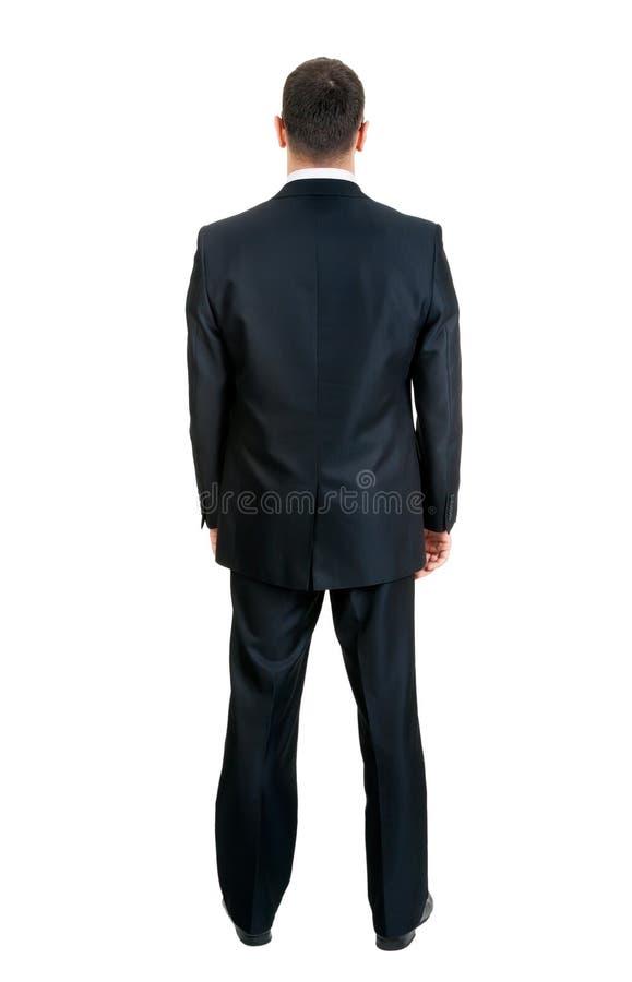 Uomo d'affari che si leva in piedi con suo di nuovo allo studio fotografie stock