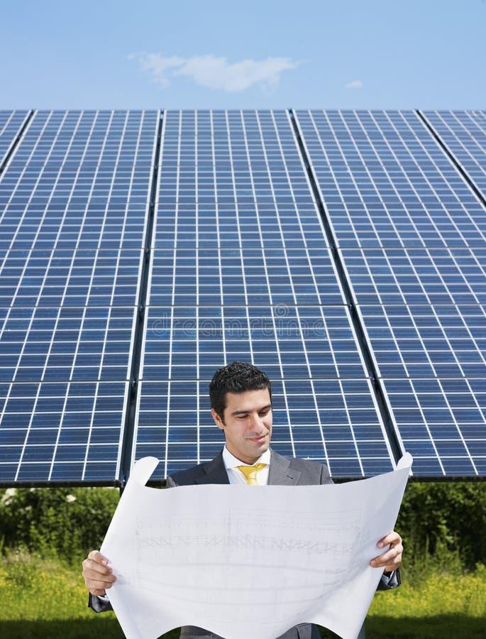 Uomo d'affari che si leva in piedi vicino ai comitati solari immagini stock